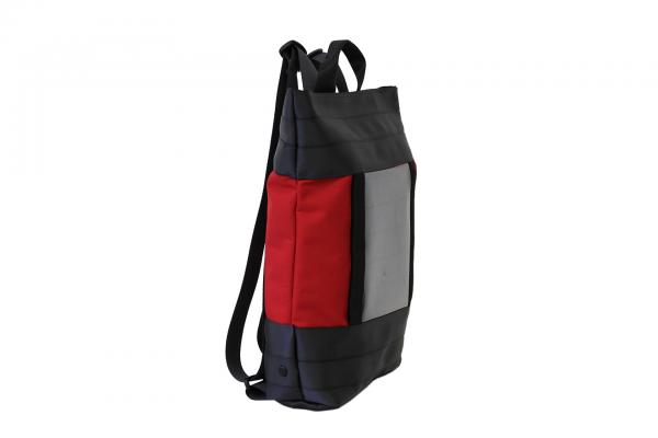Zaino in tessuto rosso e cinture di sicurezza con pannello solare visto di lato